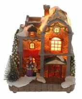 Kersthuisje met vrouw en kind met verlichting